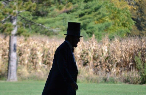 Shadowed profile of Abraham Lincoln in top hat walking in front of a field of corn.