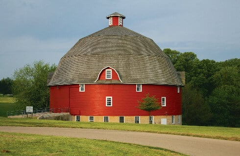 Big round red barn with a grey roof in front of a dirt road.