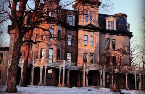 Large Gothic-style red brick house with four stories in the winter time.
