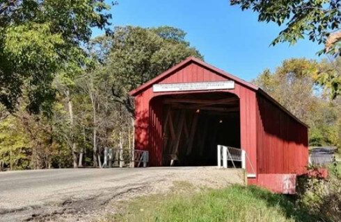 Road leading into a red covered bridge