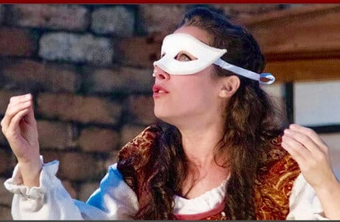 Long-haired brunette in Elizabethan clothing with a white eye mask.