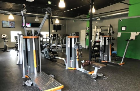 Pilates and weight machines in a modern gym setting.