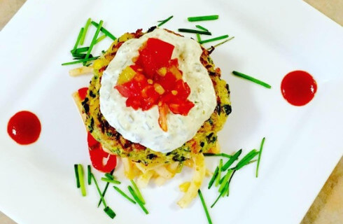 Poached egg over potato cake garnished with herbs and tomatoes.