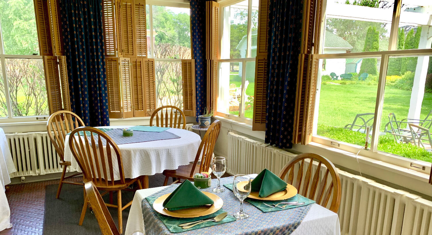 Bright breakfast room with tales for two to four set with white cloths.