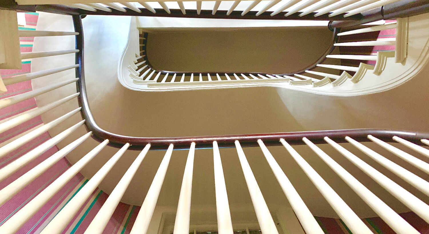 View of staircase spindles winding up from the bottom level.