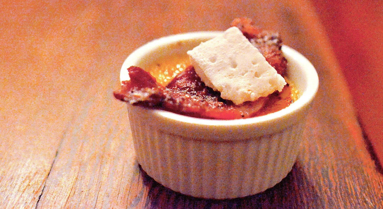 Cheesey dish baked in a white ramekin and garnished with bacon.