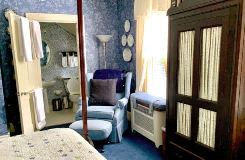 Large four-post bed in a room decrated in blue with a wingback chair and wooden armoire.