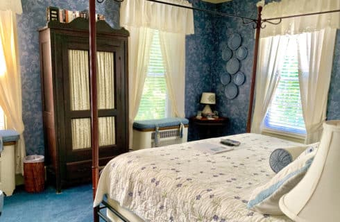 Blue bedroom with a wooden armoire and four poster bed with a cream spread.