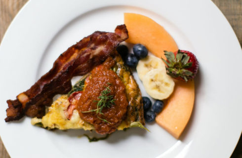 Quiche with bacon and fruit on a white plate.