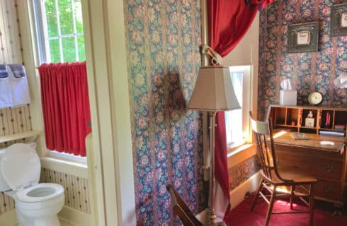 Bright bedroom with flowered wallpaper, burgundy drapes and a writing desk with view to bathroom.