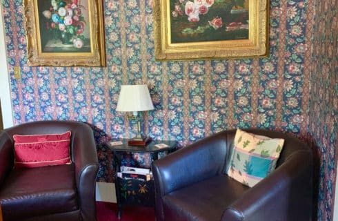 Two leather club chairs sit under wall paintings in a bedroom.