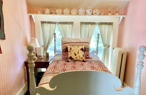 Cute single bed made up in soft coverings in a pink room with a double window.