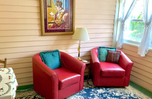 Two red club chairs with green pillows in a sitting porch with bright windows.