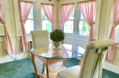 Sitting area with a glass-topped table and two cahirs surrounded by windows dressed in rose curtains.