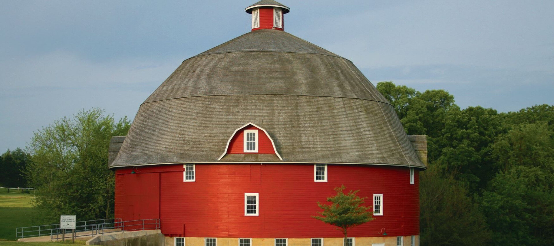 Big round red barn with a grey roof in front of a dirt road