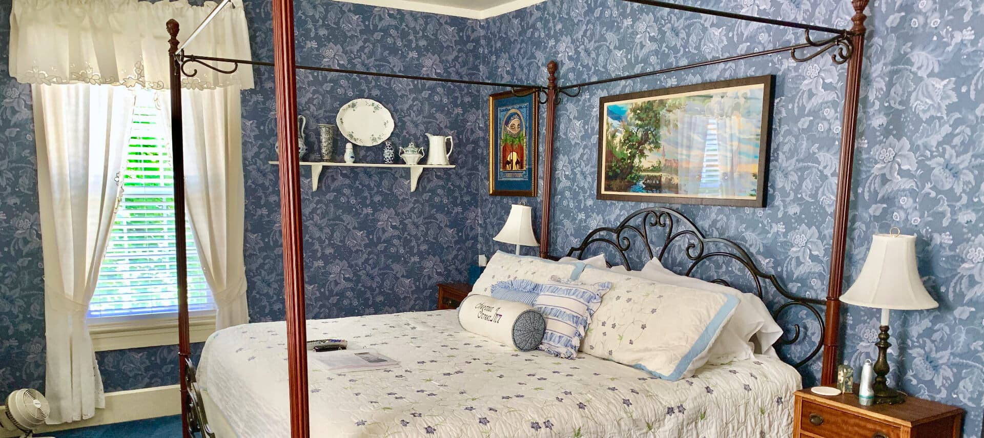 Lovely bedroom decoted in blues and creams with a wooden four-post bed and bright windows.