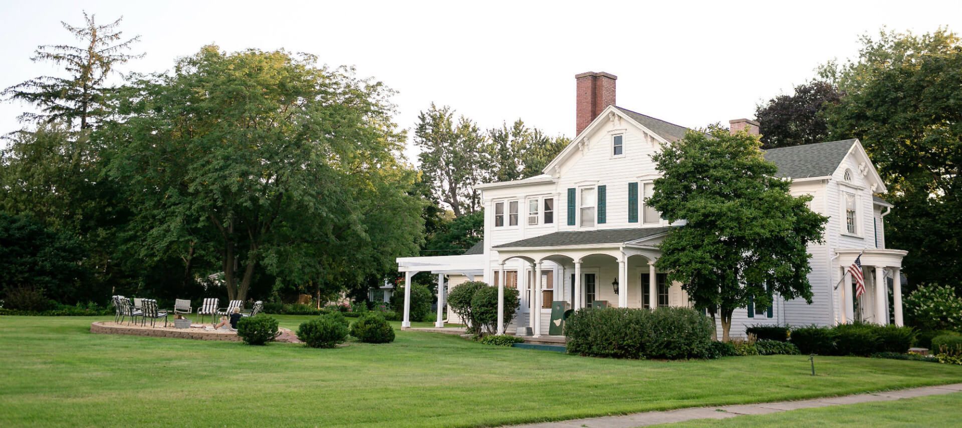 Large white historic home with two stories and a covered porch.