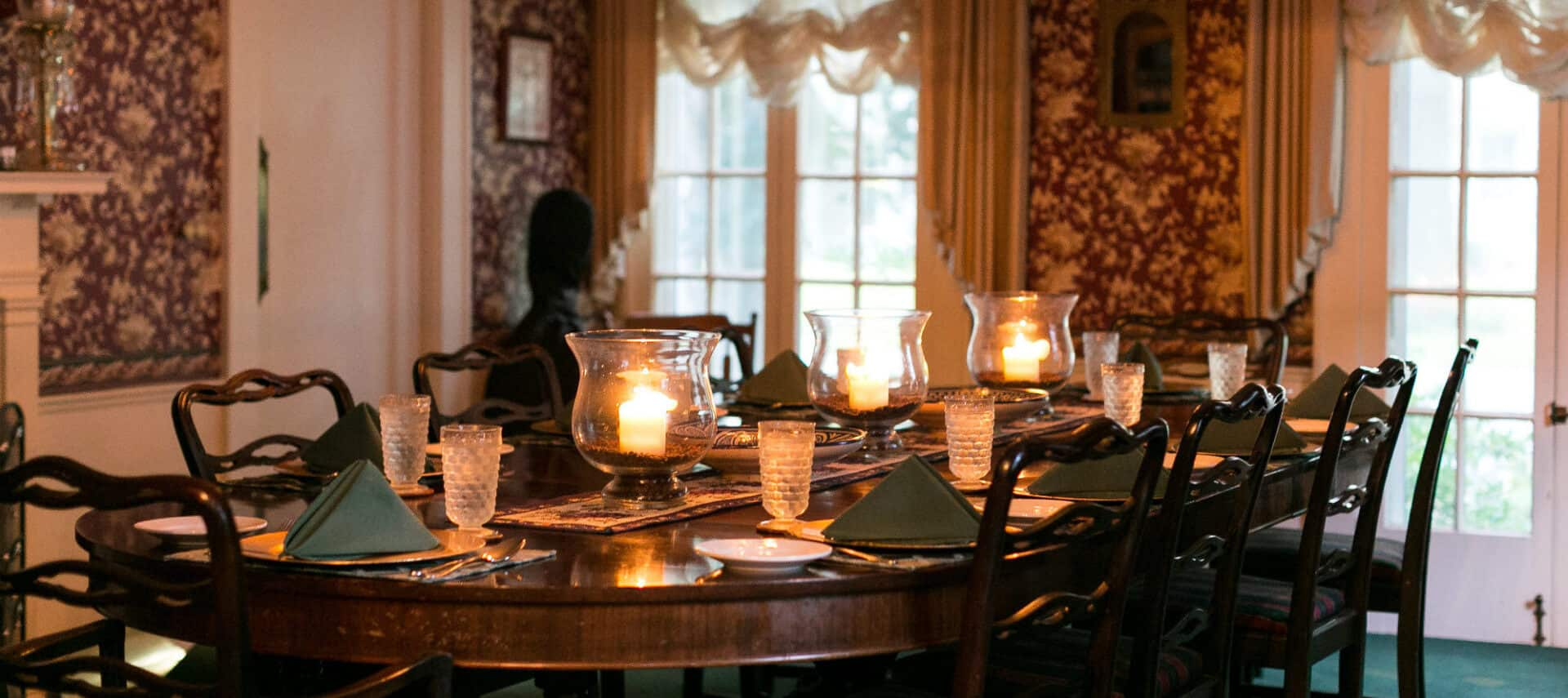 Elegant dining room containing a long table set for dinner with hurricane lamps.