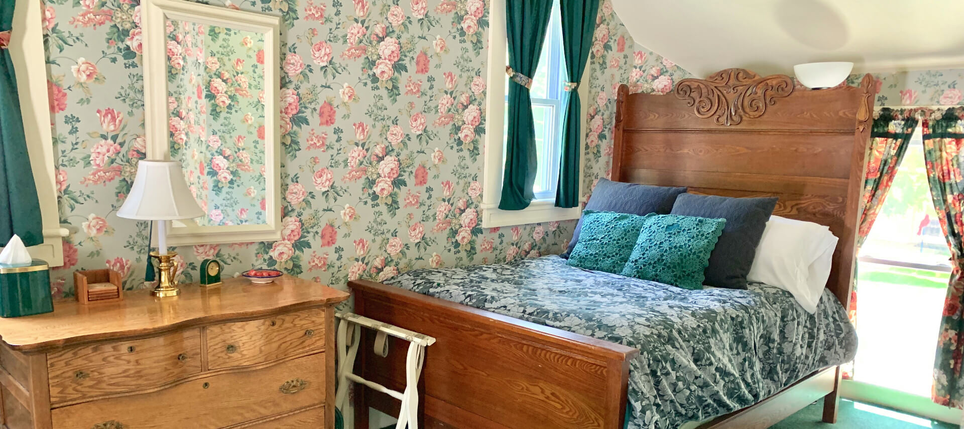 Wooden double bed made up in green in a bedroom with a dresser and green and roses wallpaper.